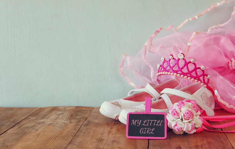 Small girls party outfit: white shoes, crown and wand flowers next to small chalkboard with phrase MY LITTLE GIRL. On wooden table. bridesmaid or fairy costume royalty free stock photography