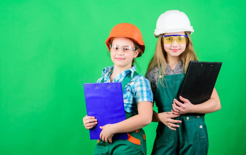 Small girls repairing together in workshop. Child care development. Future profession. Builder engineer architect. Kid. Worker in hard hat. Tools to improve stock photos