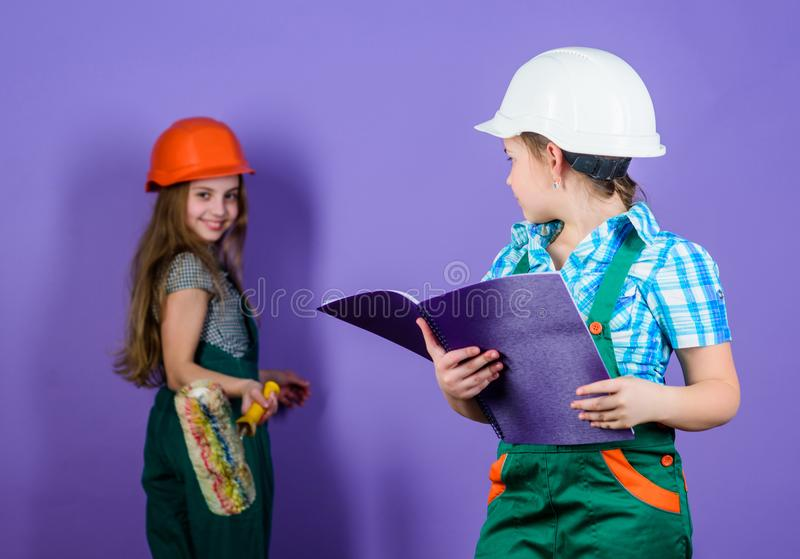 Small girls repairing together in workshop. engineering idea. Future career. Little kids in helmet with roller. Labor stock image