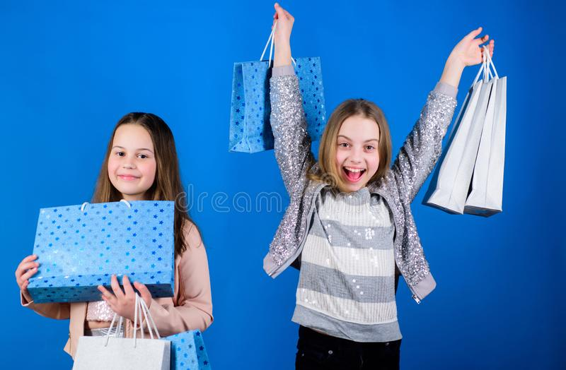 Small girls with shopping bags. Sisterhood family. savings on purchases. Kid fashion. Blue backdrop. Sales discounts stock photos