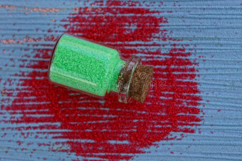 Glass bottle with green sand lies on a blue table in red sand stock image