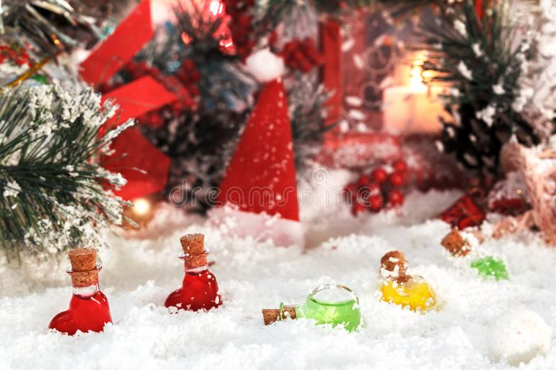 Small glass bottles in the snow on the background of New Year`s decorations, Santa`s caps and a red lantern. Magic Christmas and New Year stock photo