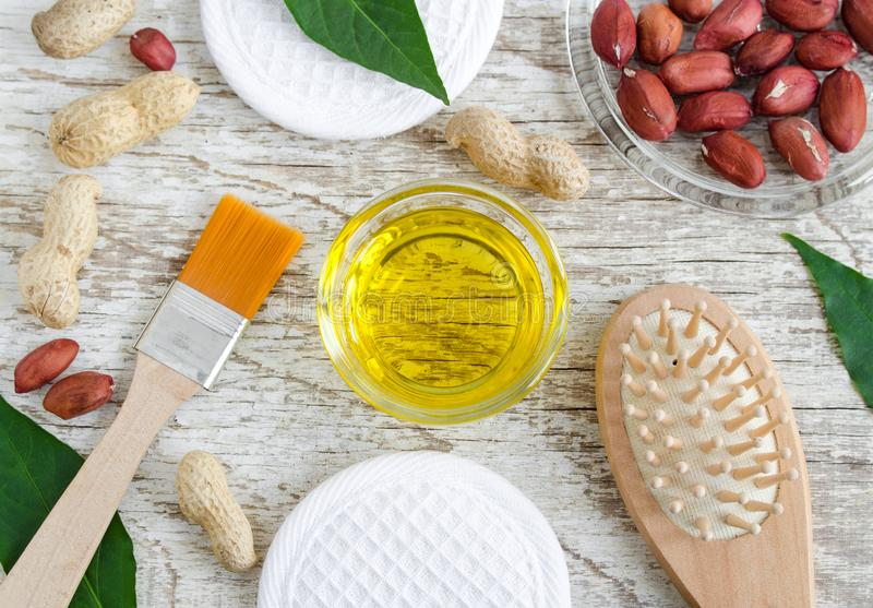 Small glass bowl with peanut groundnut oil for preparing face and hair mask. Natural skin and hair mask recipe. Ingredients of homemade cosmetics. Top view stock image