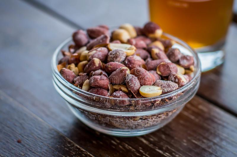 Small glass bowl with salty peanut. And glass of beer in background in cafe in Belgrade, Capitol of serbia, on the Balkan peninsula in southeastern europe royalty free stock photos
