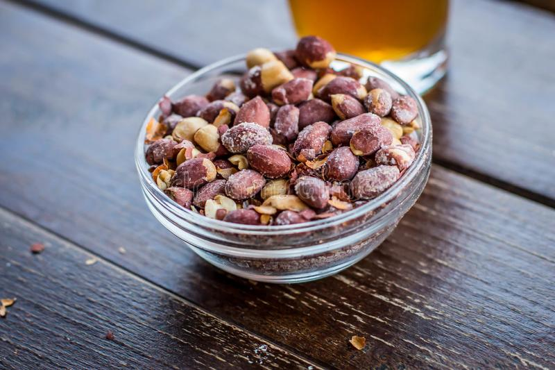 Small glass bowl with salty peanut. And glass of beer in background in cafe in Belgrade, Capitol of serbia, on the Balkan peninsula in southeastern europe royalty free stock image