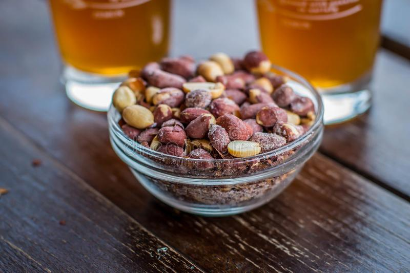 Small glass bowl with salty peanut. And glass of beer in background in cafe in Belgrade, Capitol of serbia, on the Balkan peninsula in southeastern europe stock photo