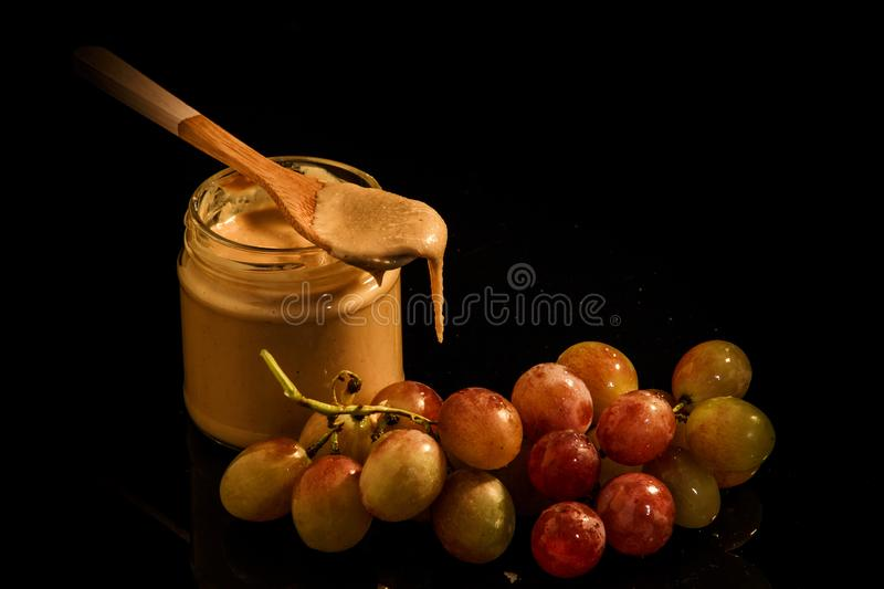 Small glass jar with creamy peanut butter next to purple grapes stock photography
