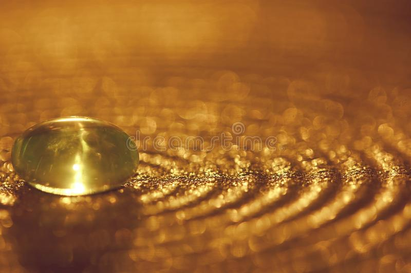 Small glass stone on a plate with golden sparkles and bokeh royalty free stock images