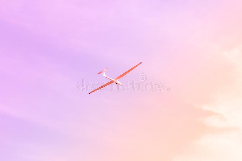 Small glider flying against the pink sky, concept of dream, happy future and positive outlook on life.  royalty free stock photos