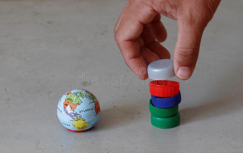Small globe and hand stacking pet bottle tops representing plastic pollution and the need for recycling. royalty free stock photos
