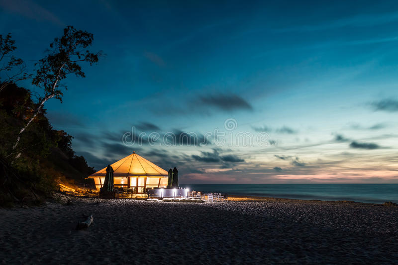 Small glowing bar by the sea at sunset stock photos