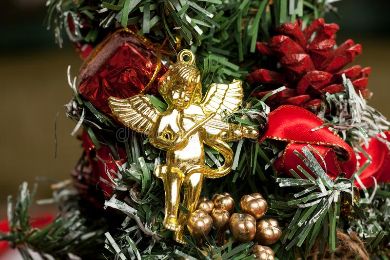 Small golden angel doll on a christmas tree macro shot.  royalty free stock images