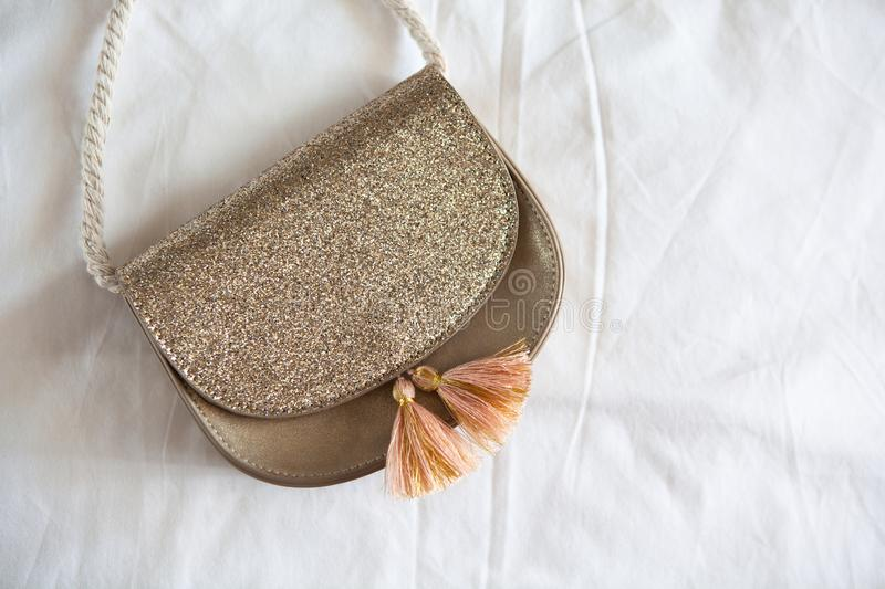 Small golden saddle handbag with tassels and rope handle lies on rumpled white sheet. Concept fees, outfitting, kid`s fashion stock photo