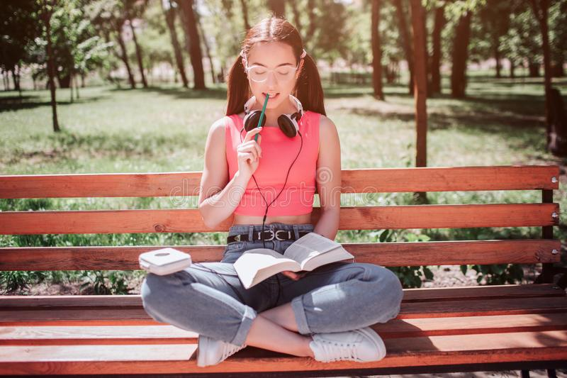 Small and good-looking girl is sitting on bench and reading a book. She has crossed her legs and chewing a piece of stock image