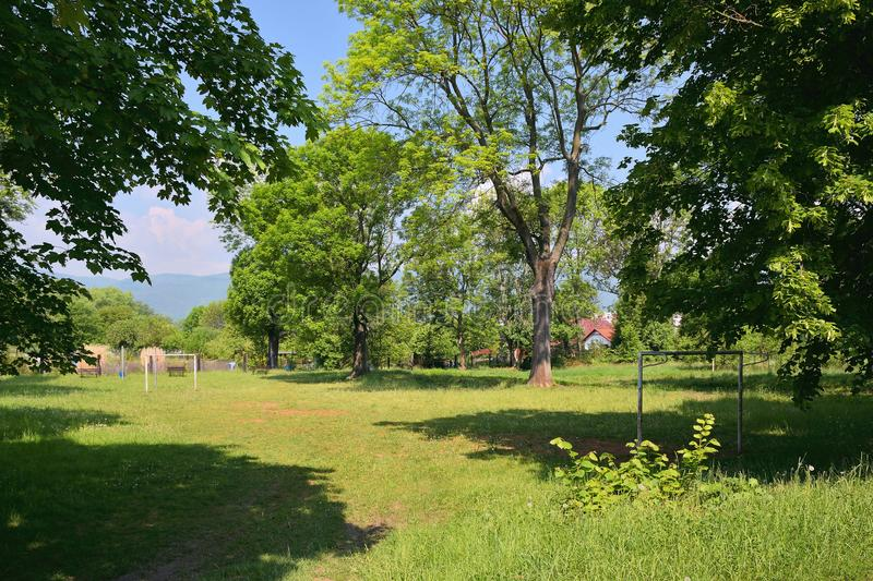 Small grassy football field between trees in czech town of Chabarovice with Ore mountains on background in spring royalty free stock photos