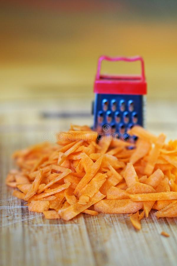 A small grater and a large carrot on a cutting board, in the kitchen. Optical illusion. Close-up. Shallow depth of field stock photography