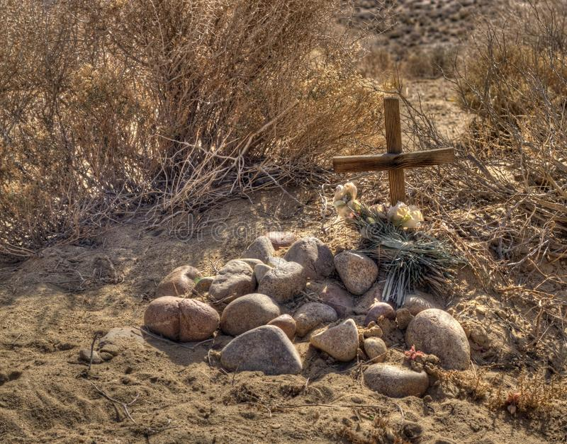 Small grave in the desert. Rustic wooden cross and round stones mark a grave in the desert with brush in the background royalty free stock image