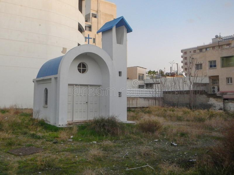 Small greek church in an industrial surroundings royalty free stock photos