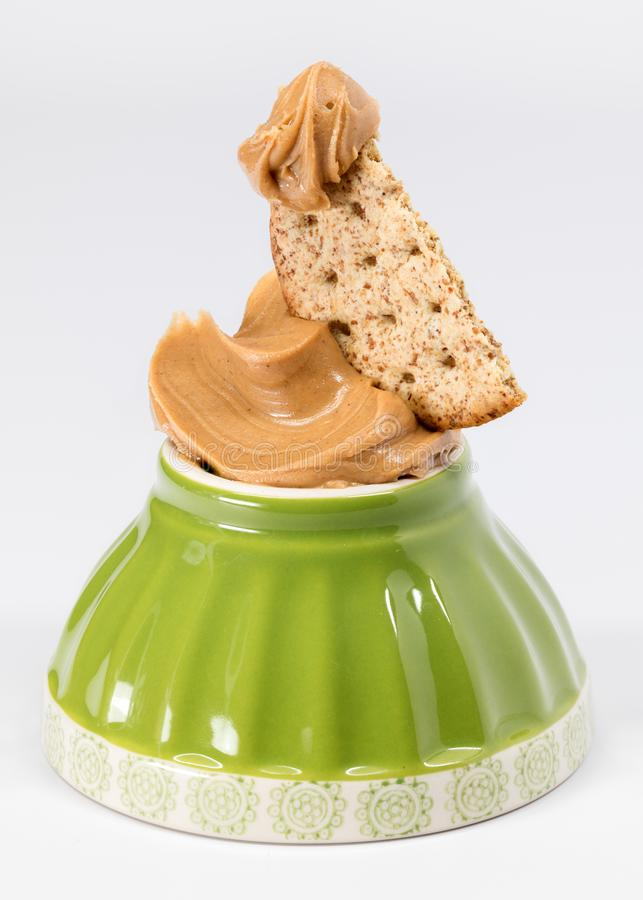 Small green bowl upside down with peanut butter and cracker royalty free stock image