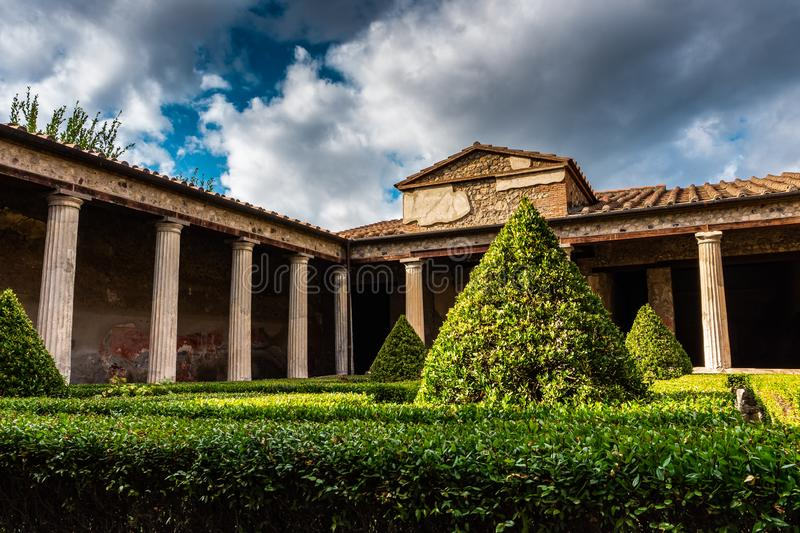 Small green courtyard of the house or villa in Pompeii, the ancient Roman city. Destroyed eruption of the volcano Mount Vesuvius stock photo
