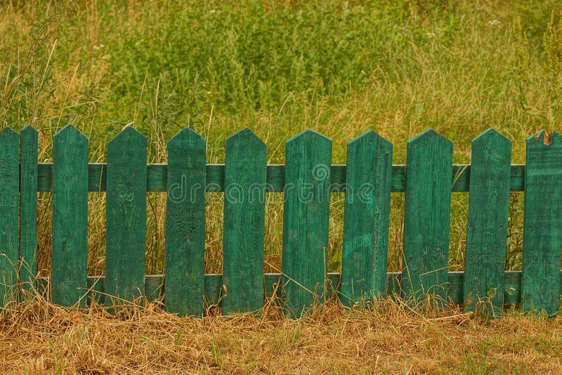Small green decorative wooden fence in tall grass stock photo