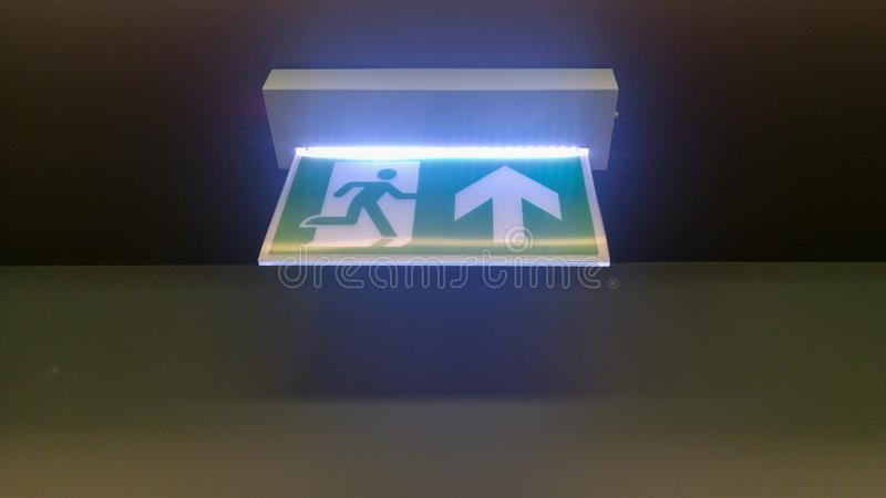 Small green emergency exit sign in office royalty free stock images