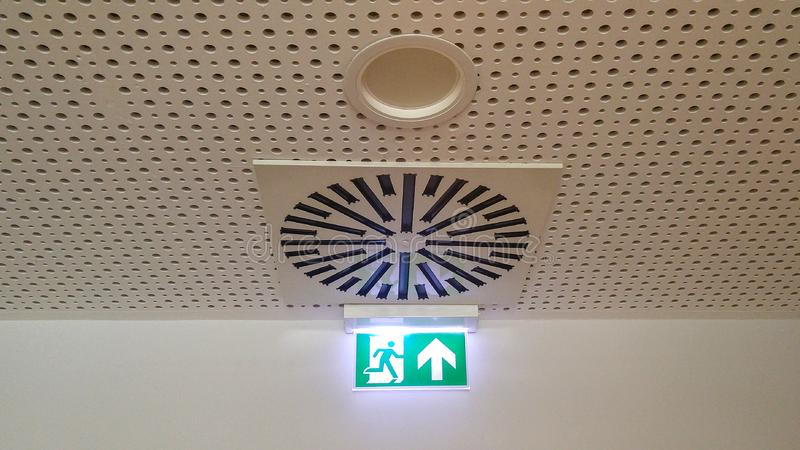Small green emergency exit sign in office stock photography