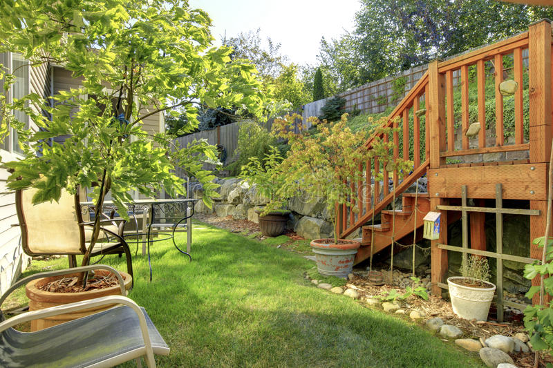 Small green fenced back yard with garden. stock images