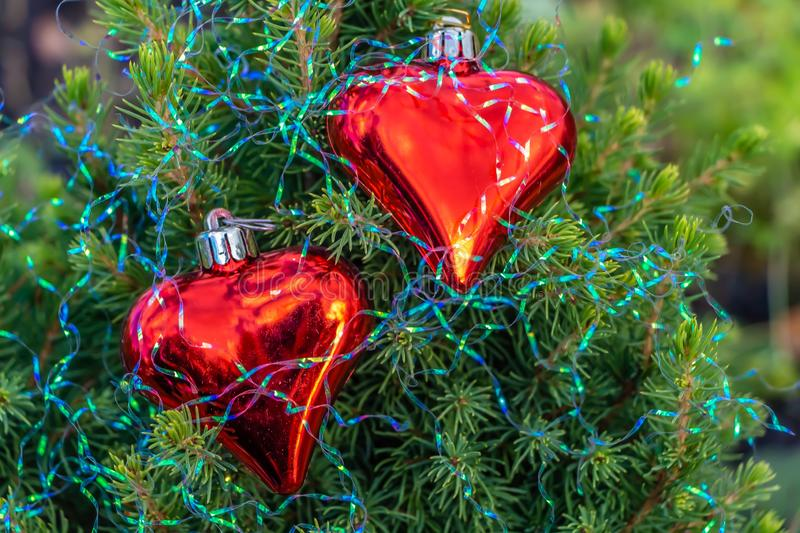 A small green fir tree with two red glass hearts with rainbow Christmas decorations stock images