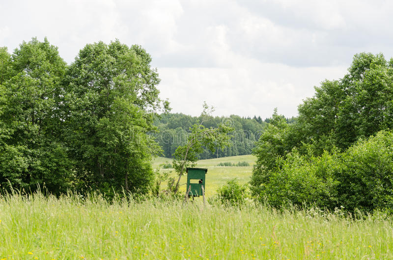 Small green hunter watch tower in nature. Forest scenery stock photography