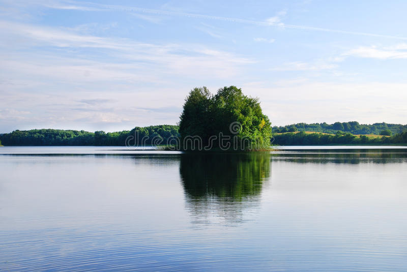 A small green island reflecting in a blue lake royalty free stock photography