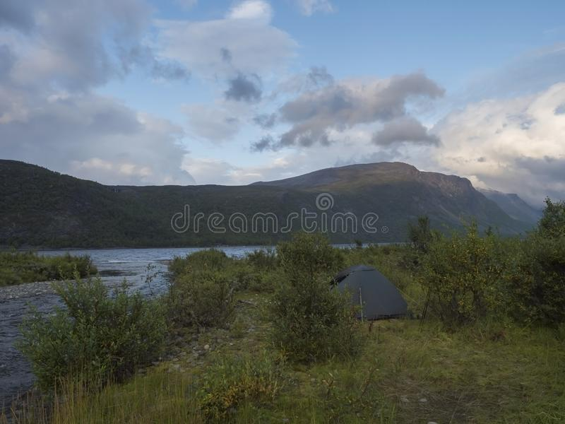 Small green tent in Beautiful wild Lapland nature landscape with blue river, Teusajaure lake, birch trees and mountains. Northern. Small green tent in Beautiful stock photo
