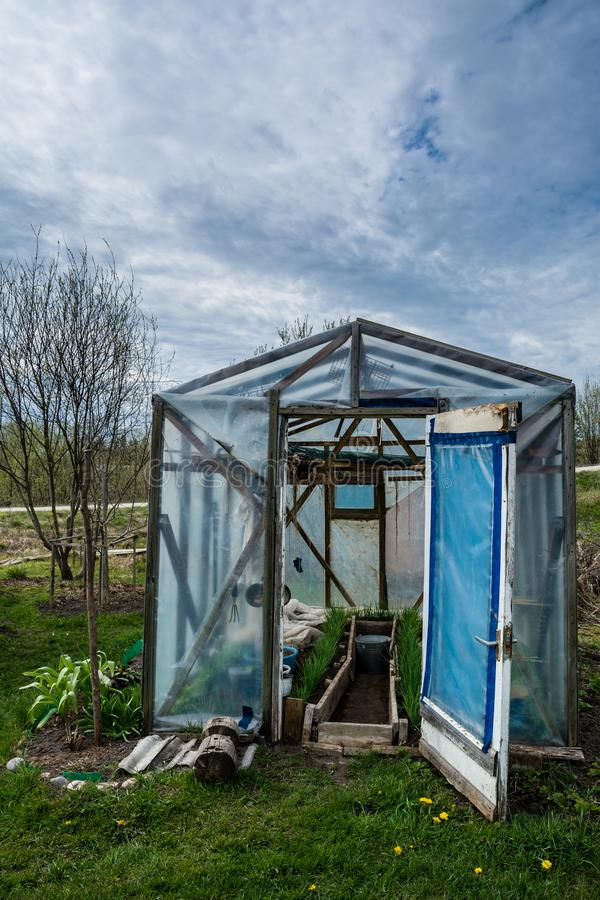 Small greenhouse with doors opened in a garden in spring at day. Naked trees and grass in surrounding royalty free stock photography