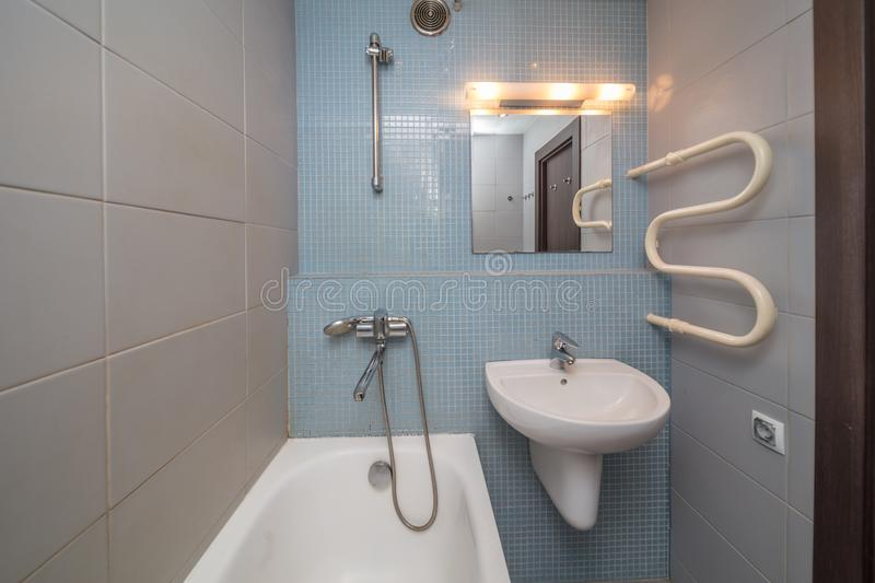 Small grey bathroom. Small grey tile bathroom with bath tube and sink stock image