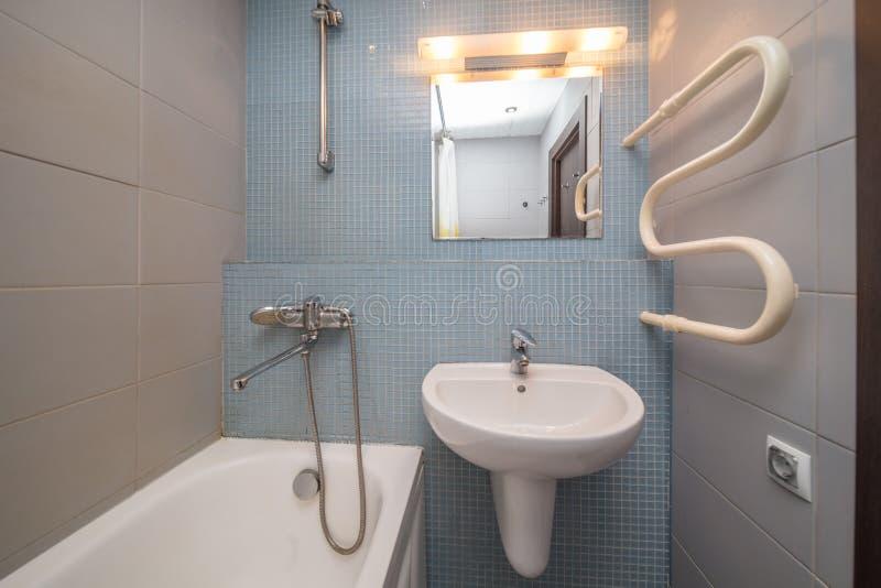 Small grey bathroom. Small grey tile bathroom with bath tube and sink royalty free stock photos