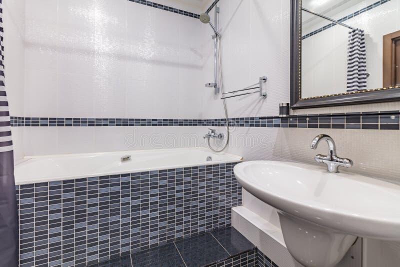 Small grey bathroom. Small grey tile bathroom with bath tube and sink stock photos