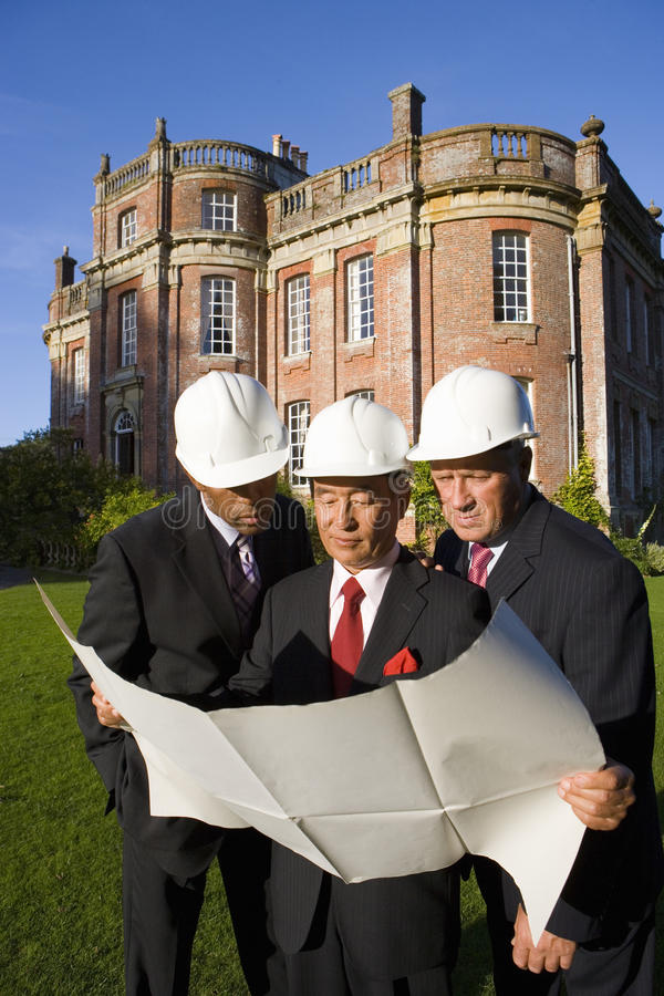 Small group of businessmen in hardhats looking at blueprint by manor house royalty free stock images