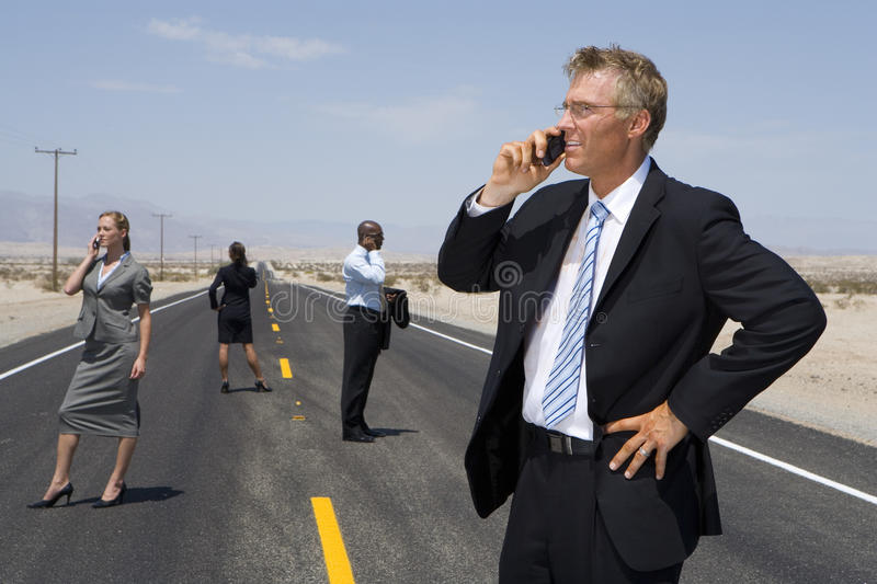 Small group of businessmen and women using mobile phones on road in desert, side view stock photography