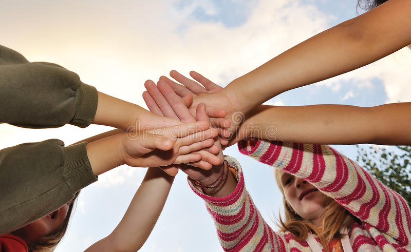 Small group of happy children outdoor. Their hands stock image