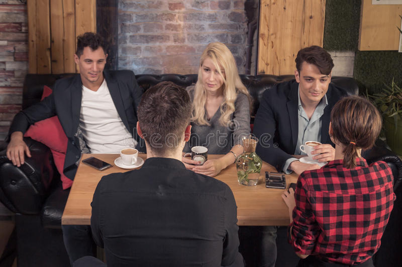 Small group of people talking, sitting sofa, coffee shop table i royalty free stock photo