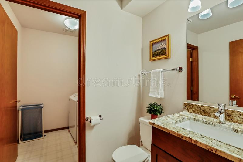Small guest Bathroom with wood vanity and open door.  royalty free stock photography
