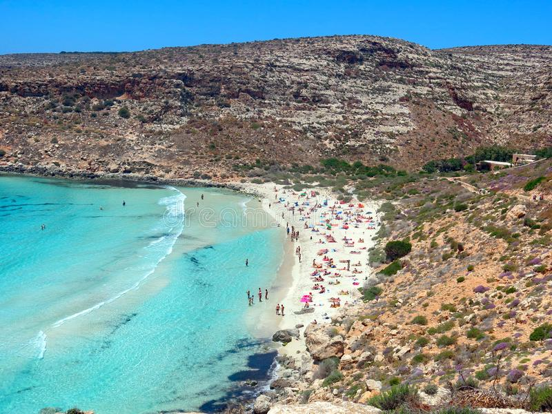 Small gulf with the blue sea and the bathers on the beach. Beautiful panorama of a small gulf with the blue sea and the bathers on the beach in summer stock photography