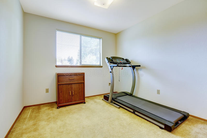 Small gym room. Bright gym room with one window and carpet floor. Running exercise equipment and wooden cabinet royalty free stock photos