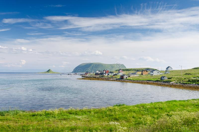Small hamlet on the shore of Mageroya. Grassy shore of the bay with a small village in the north island Mageroya royalty free stock photography
