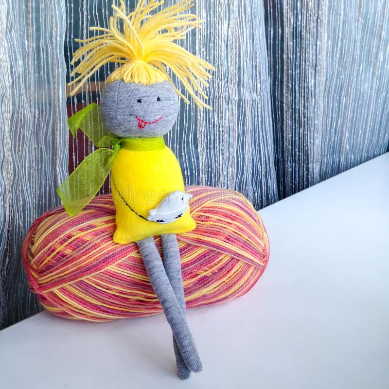 A small handmade doll sits with his legs crossed on a ball of colored woolen threads. She has yellow dreadlocks hair, a dress, a green bow and a gray bird in stock image