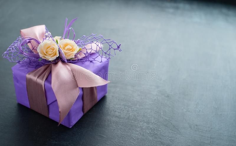 small handmade purple gift box with little pastel roses and ribbon on dark background, copy space for text stock images