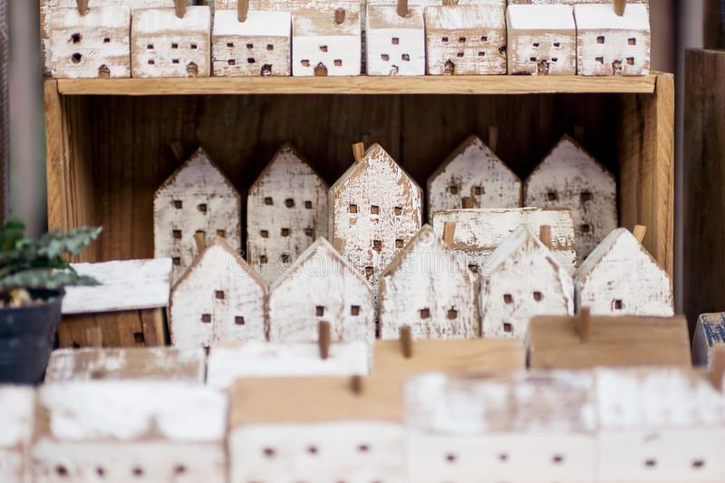 Small handmade wooden houses in a row on store shelf. Craft, home decor concept. Scandinavian, country style royalty free stock photos