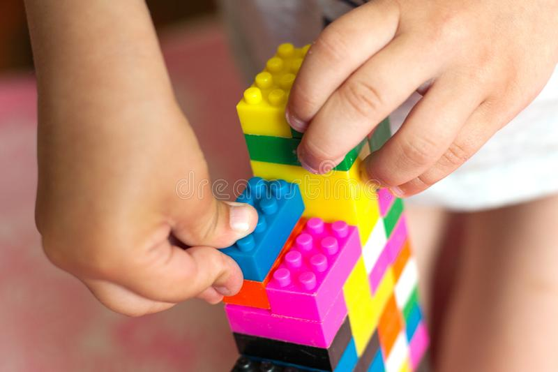 Small hands of the child collects the bright plastic colored Designer. Educational toys and Early learning stock photo