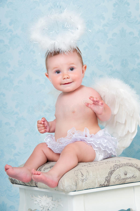 Small and happy angel smiling and sitting on a chair. Small and happy angel smiling and sitting on a chair stock photos
