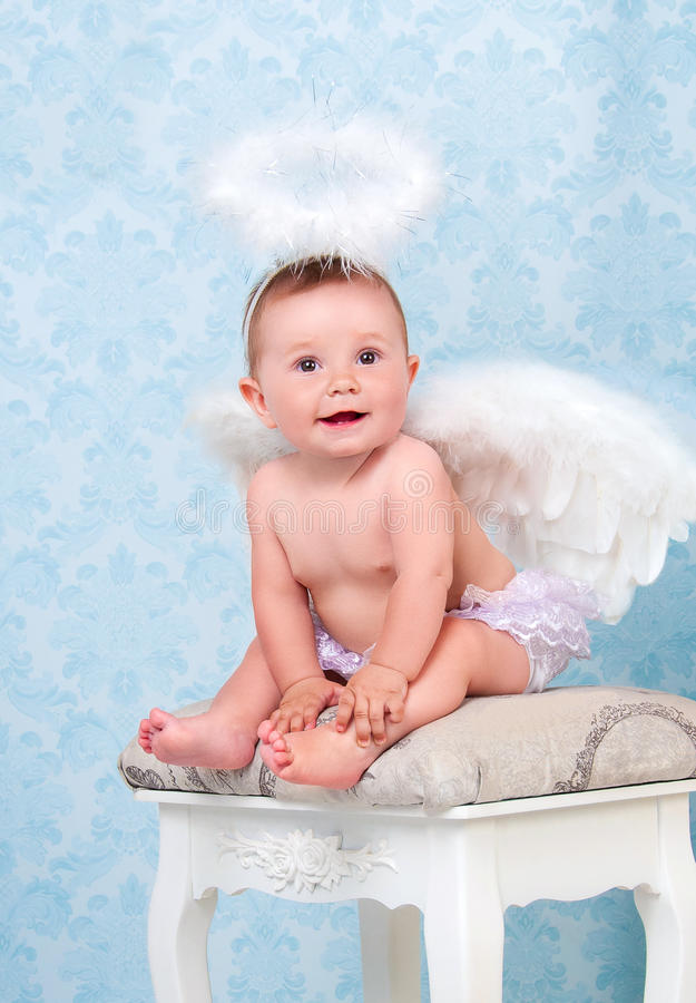 Small and happy angel smiling and sitting on a chair. Small and happy angel smiling and sitting on a chair royalty free stock photos